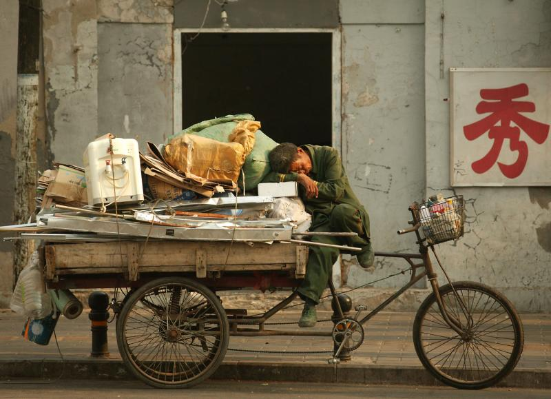A Chinese migrant collecting recyclable trash takes a late afternoon nap on his 'flatbed' tricycle in Beijing on May 14, 2009. (Photo: UPI Photo)