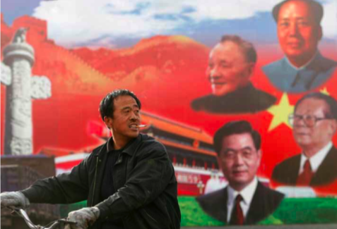 A cyclist in Taiyuan rides past a billboard displaying political leaders past and present - from the top, Mao Zedong, Deng Xiaoping, Jiang Zemin and Hu Jintao