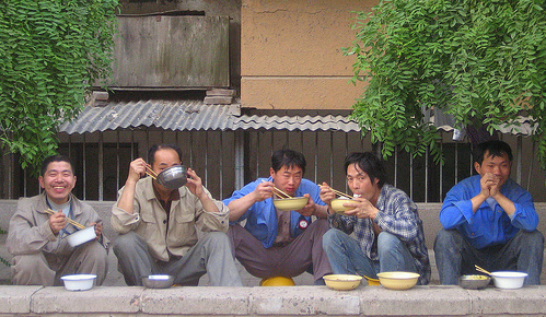 Migrant workers eating and resting sitting on their helmets, on the fence of their constuction site and temporary home (Photo: Flickr user '! ! JJJJJJJ')