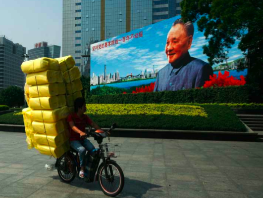 In Shenzhen, a man on a laden motorised bicycle rides past a poster of former leader Deng Xiaoping. (Photo: Bobby Yip/Reuters)