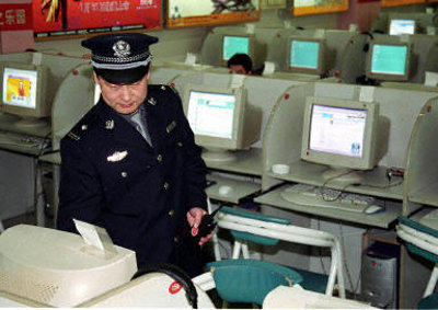 A security official monitors internet usage in a cyber cafe in China.