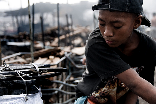 A child worker transporting wood he has collected from a dump site to an outside charcoal factory in Manilla, the Philippines on November 17, 2008. (Photo: Flickr user 'Mio Cade (in Bali)')