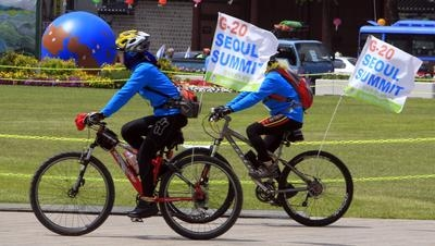 Volunteers on bicycle carry banners of G20 Summit in Korea in Seoul, South Korea, on May 10, 2010. (Photo: AP Photo/Lee Jin-man)