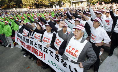 Protesters clench their fists as they oppose Japan joining the US-backed Trans-Pacific Partnership, in Tokyo on November 10, 2010. The banner reads, 'We are dead against joining in TPP.' (Photo: AP Photo/Kyodo News)