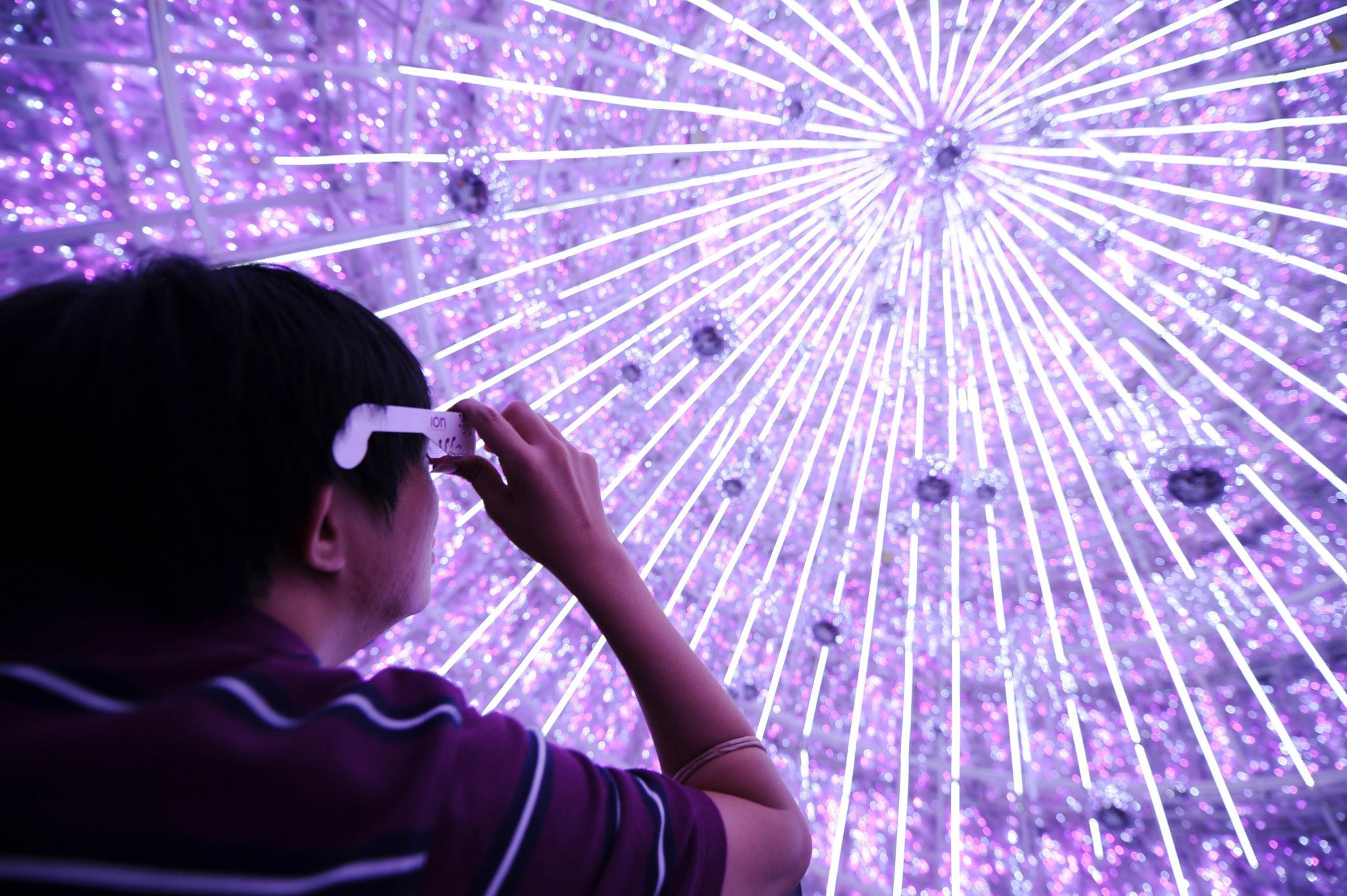 A man looks through a magnifying glass inside a six-storey high LED based decorated Christmas tree in front of Ion shopping mall on Orchard Road in Singapore. (Photo: AAP)