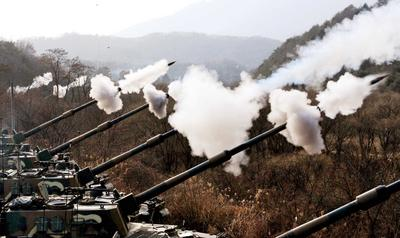 South Korean Army K-9 155mm self-propelled Howitzers fire rounds during air and ground military exercises on the Seungjin Fire Training Field, in mountainous Pocheon on December 23, 2010. (Photo: AAP)