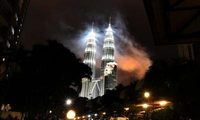 Smoke floats in the air after a six-minute fireworks show during the New Year celebrations at the landmark Patronas Twin Towers in Kuala Lumpur on January 1, 2011. (Photo: AAP).