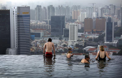Tourists relax in an infinity pool on the roof of the Marina Bay Sands Hotel tower on Monday Jan. 3, 2011 in Singapore. Two huge new casino resorts, which together cost more than $10 billion to build, are the crown jewels of a decade-long effort to diversify the island's economy toward services such as tourism and finance and lessen dependence on manufacturing. (Photo: AAP)