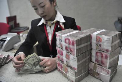 A teller counts US and Chinese currencies at a branch of Huaxia Bank in Shenyang, northeast China, 14 January 2011. The Chinese currency reached a new high of 6.5977 against the US dollar. The move came ahead of the 18-21 January visit to the United States by President Hu Jintao. (Photo: AAP)
