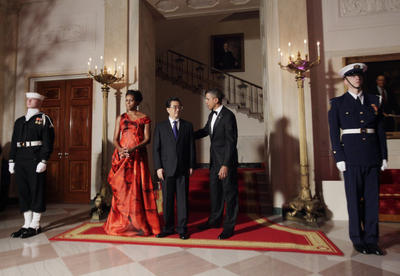 President Barack Obama and first lady Michelle Obama stand with China's President Hu Jintao at the Grand Staircase as they arrive for a state dinner at the White House in Washington, Wednesday, Jan. 19, 2011. (Photo: AAP)