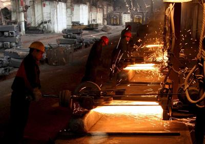 Chinese workers cut off metal blocks in Xining Special Steel Works, a state-owned steel maker, in Xining, Qinghai province, Tuesday, 15 November 2005. (Photo: AAP)