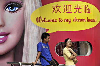 A man and a woman stand in front of a shop showing Barbie, product of US toy manufacturer Mattel, in Shanghai. Since the US consumer is no longer the main growth engine of the global economy, experts are looking at China but are sceptical the Asian giant can fill that huge role. (Photo: AAP)