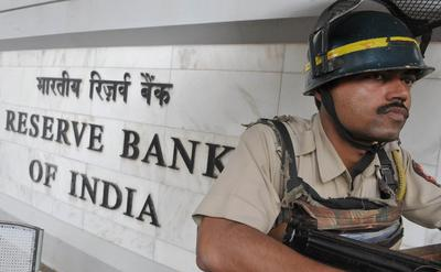 An Indian police personnel stands guard outside the headquarters of The Reserve Bank of India in Mumbai on July 27, 2010. (Photo: AAP)