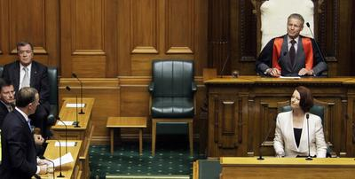 Australian Prime Minister Julia Gillard (R-front) listens to a reply by New Zealand Prime Minister John Key (L) during her address to politicians in the parliamentary debating chamber in Wellington on February 16, 2011. (Photo: AAP)