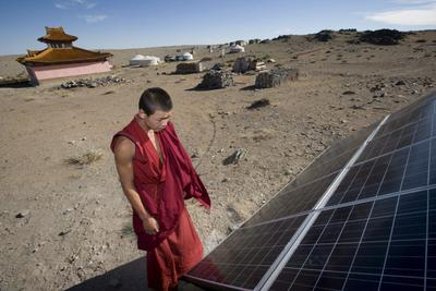 A Mongoiian Lama Buddhist monk tends to the solar powered electricity generator at a monastery deep in the Gobi desert in Mongolia, 10 August 2007. (Photo: AAP)