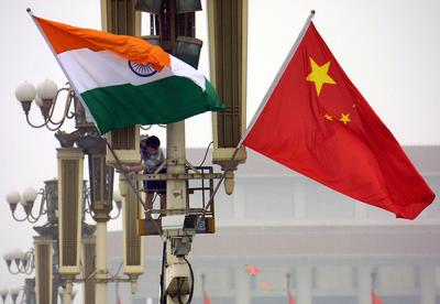 Workers put up the Indian flag alongside the Chinese flag on Tiananmen Square. Will their post Cold War balance of power arrangements continue or will their be a newer liberalised Asia. (Photo: AAP)