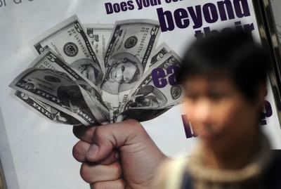 A pedestrian walks past an advertisment featuring US dollar bills in Hong Kong on April 6, 2011. (Photo: AAP)