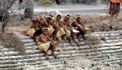 Locals in traditional dress sit on sand bags in Tarawa, Kiribati. (Photo: AAP)