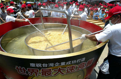 Employees of a Taiwanese instant noodles company stir a giant instant noodle dish alleged to be the biggest in the world during a publicity stunt on June 5 2004 in Taichung, Taiwan. (Photo: AAP)
