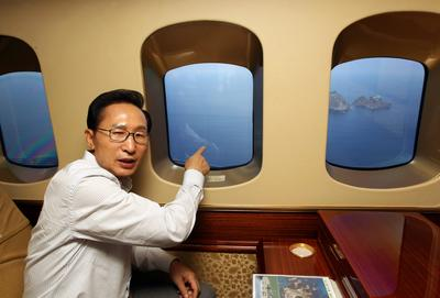 Former South Korean president, Lee Myung-bak points to the disputed islets of Dokdo (called islets of Takeshima in Japan) from a helicopter, 10 August 2012.