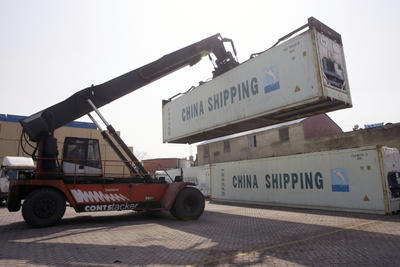 A crane carries a shipping container up at the storage of China Shipping Container Lines Co. in Shanghai on 10 March 2010. China will likely develop Gwadar port quickly by making a bigger investment than the PSA, but its current interests appear commercial, aimed at securing its energy supplies. (Photo: AAP)