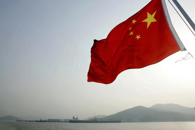 A Chinese flag flutters in the wind as an oil tanker is anchored offshore in the distance near Zhoushan, China. Chinas push into the Indian Ocean is an inevitable part of its need to develop efficient supply routes across the back of Asia for energy and resource supplies out of the Middle East and Africa. (Photo: AAP)