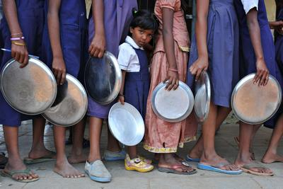 Indian schoolchildren wait in line for their midday meal at a government primary school in the outskirts of Hyderabad. (Photo: AAP)