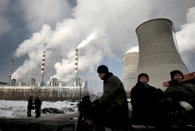 Workers cycle past a coal-fired power plant on a tricycle cart in Changchun, in northeast Jilin province, China. (Photo: AAP)