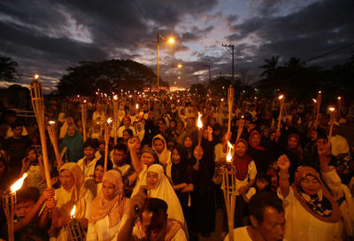 Filipino Muslim women carry torches as they join a rally at the Maharlika village in suburban Taguig, south of Manila, Philippines, on Wednesday 6 March 2013. The group is calling for a peaceful resolution to the current crisis. (Photo: AAP)