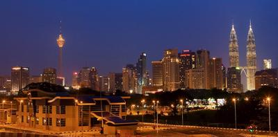 Buildings illuminated at night in Kuala Lumpur, Malaysia on 24 May 2006. Government-linked corporations control more than half the industry share of operating revenue in utilities, including electricity. (Photo: AAP)