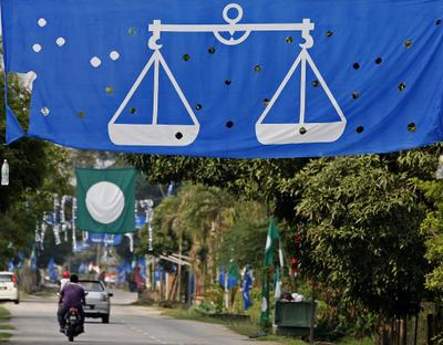 Rows of political party flags hung across a road to woo voters for the upcoming general election in Pekan, 300km outside Kuala Lumpur, Malaysia, 21 April 2013. (Photo: AAP)