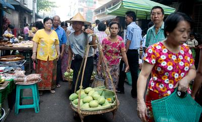 A merchant carries fruits across a market in Rangoon in Myanmar on 30 April 2012. The growth potential of Myanmar is enormous as it sheds the shackles of policies that have condemned it to poverty over the past fifty years. (Photo: AAP)