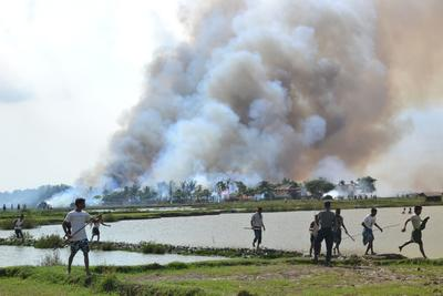 A village in flames while a soldier (4th R) stands by in the Myanmar state of Rakhine. (Photo: AFP/Human Rights Watch)