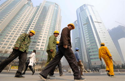 Construction workers walk past high-rise commercial buildings in Beijing 9 March 2008. If the economy is to continue to grow, even at a more moderate rate, it has to graduate from simple manufacturing production, relying on the mobilisation of labour, to growth led by industrial upgrading, driven by high rates of human capital formation and research and innovation. (Photo: AAP)