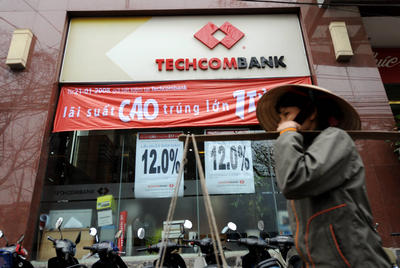 A street vendor walks past a branch outlet of the local commercial bank Techcomban in Hanoi. The lack of confidence among borrowers and investors in the banking sector, and the uncertainties of the banks over their balance sheets and the path of future regulations, have resulted in a slump in credit growth to an estimated 7 per cent in 2012, (Photo: AAP)
