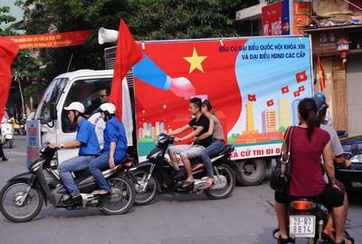 A truck bearing propaganda posters featuring the legislative elections and equipped with a loudspeaker drives in downtown Hanoi on 22 May 2011. In future, Vietnam could formalise a one-party, two-candidate system. (Photo: AAP)