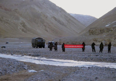 In this Sunday, 5 May 2013 photo, Chinese troops hold a banner which reads: 'You have crossed the border, please go back,' in Ladakh, India. While the recent troop standoff in a remote Himalayan desert spotlights a long-running border dispute between China and India, the two emerging giants are engaged in a rivalry for global influence that spreads much farther afield. (Photo: AAP)