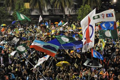Protestors wave flags as they gather at a stadium during a rally in Kuala Lumpur on 25 May 2013 to protest against the results of the  general election. Tens of thousands of people rallied near the capital on Saturday night against alleged electoral fraud, further raising the political temperature after divisive recent polls. (Photo: AAP)