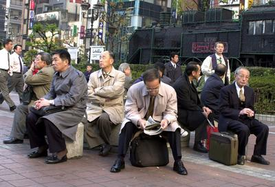 Japanese businessmen take a rest at a square outside Shimbashi railway station in Tokyo. There is now a debate in Japan over whether the country should adopt a more liberal immigration policy, especially for highly-skilled workers. (Photo: AAP)