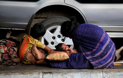 An Indian homeless family seen under a flyover in the eastern Indian city of Calcutta. Now that India has a sizeable middle class, the situation for poor Indians has worsened since the 1990s. (Photo: AAP)