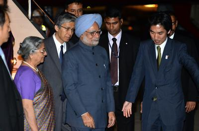 Indian Prime Minister Manmohan Singh accompanied by his wife Gursharan Kaur, is greeted by a Japanese official upon his arrival at Tokyo International Airport on 27 May 2013 (Photo: AAP).