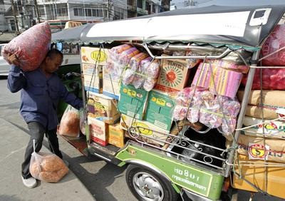 A Thai driver loads consumer goods onto a three wheeled motorized auto rickshaw taxi or Tuk Tuk in Bangkok, Thailand, 3 June 2013. (Photo: AAP)