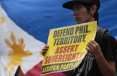 A Fililipino protester holds a slogan beside a Philippine flag during a rally outside the Chinese Consulate in suburban Makati, south of Manila, Philippines on 11 June 2013. (Photo: AAP)