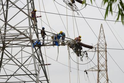 Employees work on a 132kv overhead electricity line along the Sarkhej-Gandhinagar Highway in Ahmedabad on 26 June 2013. India's border states are leading the push to export electricity to Pakistan and Bangladesh. (Photo: AAP)