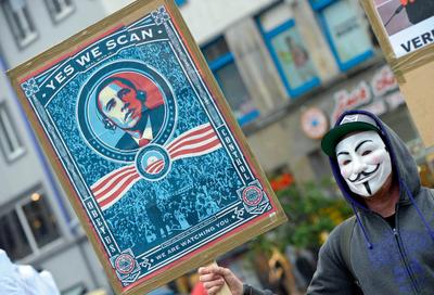 A protestor wearing a Guy Fawkes mask holds a banner with a picture of US President Barack Obama to protest against the NSA internet surveillance programme 'PRISM' on 29 June 2013 in Hannover, central Germany. (Photo: AAP)