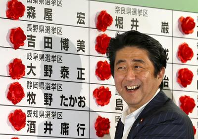 Beaming Japanese Prime Minister Shinzo Abe is all smiles as he puts red roses on the names of LDP candidates winning the upper house election on 21 July 2013 after winning the majority with coalition partner in a landslide victory in the election. (Photo: AAP)