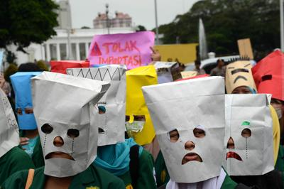Indonesian students wear masks during a protest outside the presidential palace in Jakarta on June 12, 2013 to denounce impending fuel price increases, as the government plans to reduce a fuel subsidy. (Photo: AAP)