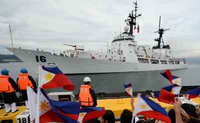 Students wave miniature national flags as a Philippine Navy high-endurance Hamilton-class cutter, the BRP Ramon Alcaraz, that had been decomissioned by the US Coast Guard and acquired by Manila, arrives at the former US naval base in Subic Bay, northwest of Manila. (Photo: AAP)