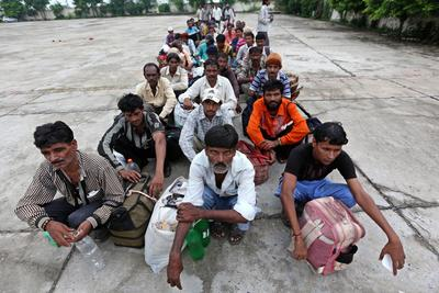 A group of Indian fishermen sits on the ground after their release from a prison as they show their temporary travel documents while crossing into India through India-Pakistan Wagah border near Lahore, Pakistan, 24 August 2013. Pakistan recently announced that it would not consider conferring most favoured nation status on India. (Photo: AAP)