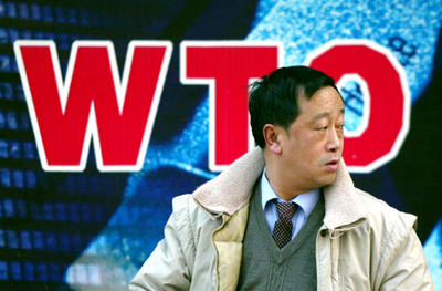 A man walks past a billboard which celebrates Chinas accession into the WTO in Beijing. (Photo: AAP)